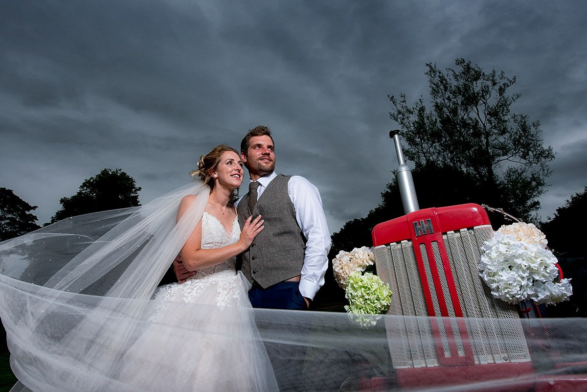 Bride and groom portrait with tractor
