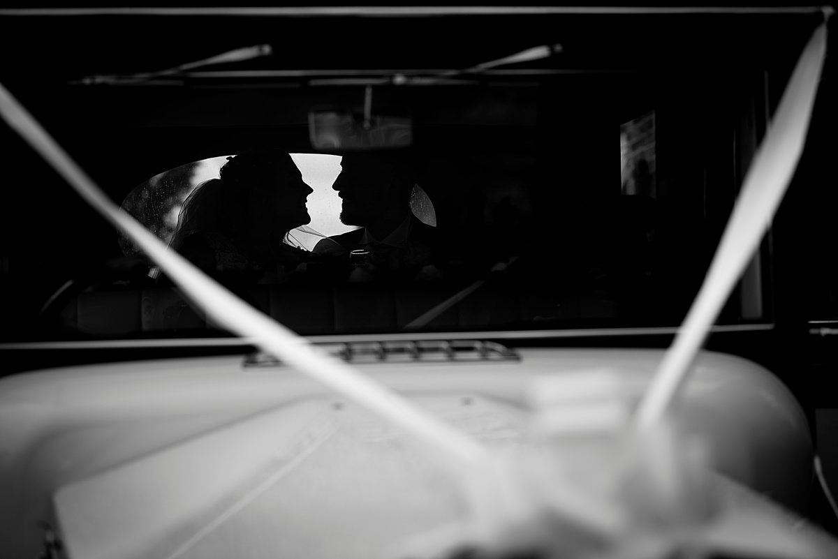 bride and groom silhouette in wedding car