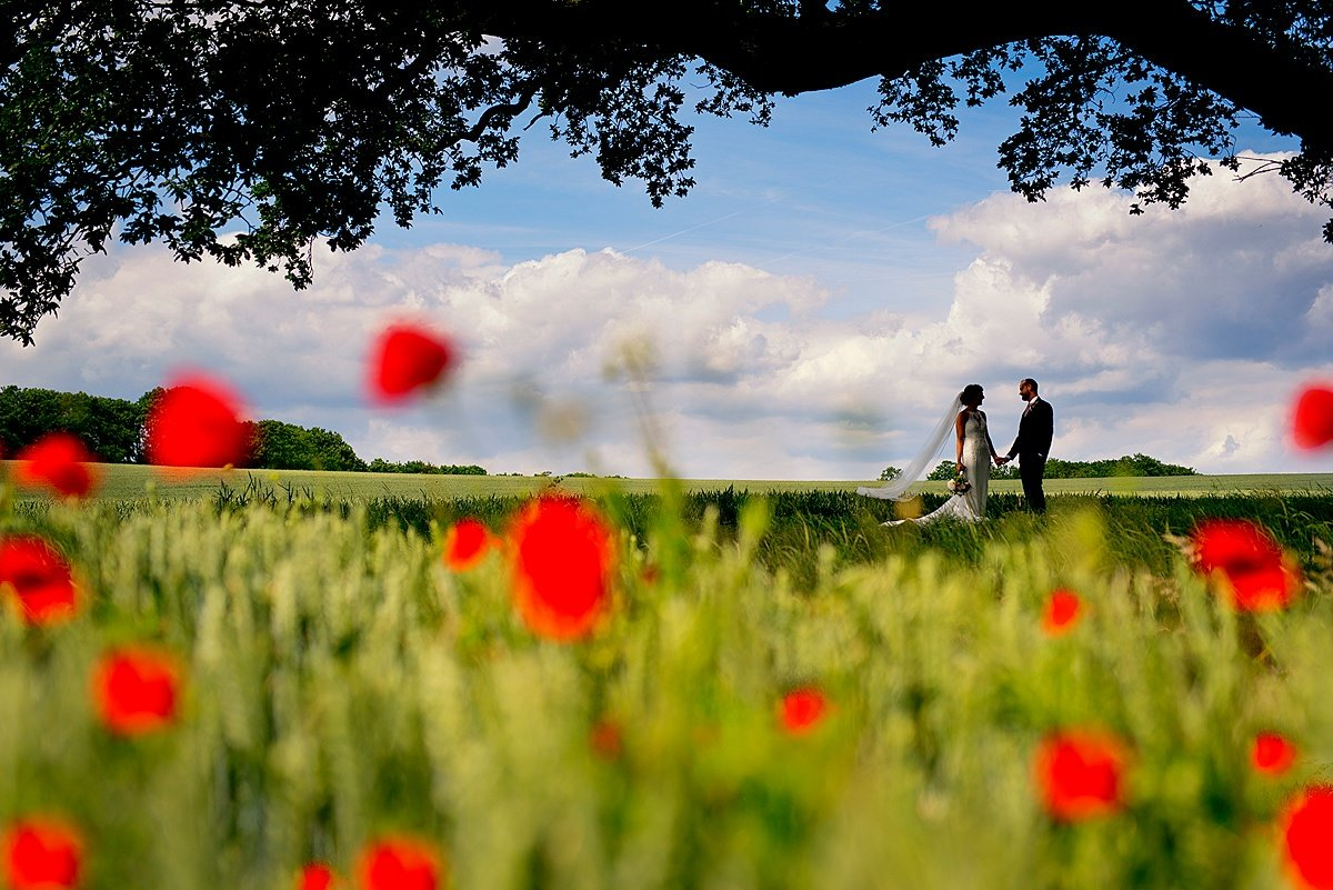 bride and groom in poppy field